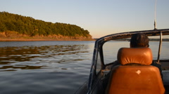 Anonymous man floats in old motorboat near shore with rock Stock Footage
