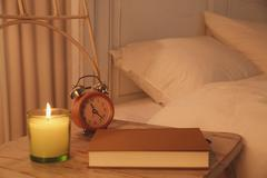Bed and aroma candle on wooden chair Stock Photos
