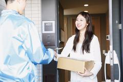 Young Japanese woman getting package from delivery man Stock Photos