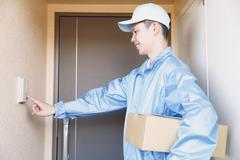 Young Japanese delivery man ringing doorbell Kuvituskuvat