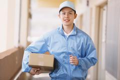 Young Japanese delivery man with box Stock Photos