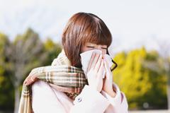 Attractive Japanese woman feeling sick on a Winter day Stock Photos