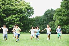 Japanese kids running in a city park Stock Photos