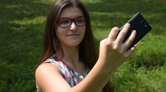 Girl making selfie photo and using mobile outdoor Stock Footage