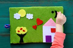 Child hand plays with Felt Creations - Quiet Books Stock Photos