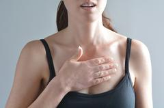 Woman having acute pain in a her chest Stock Photos