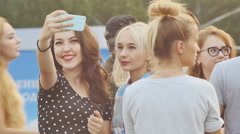 Two girls teens make a selfie in the company of young people Stock Footage