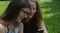 Teen girls having fun with cell outdoor Stock Footage