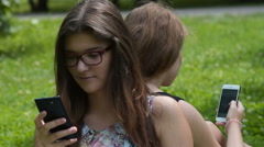 Teen friends busy with web browsing on mobile phones Stock Footage