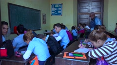 Students study in a classroom in Cuba as a teacher looks on. Stock Footage