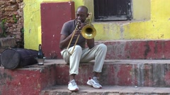 A man plays the trombone on the streets of Havana, Cuba. Stock Footage