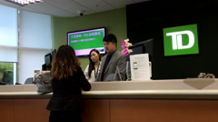 People at a bank counter talking to the teller inside TD Bank with 4k resolution Stock Footage