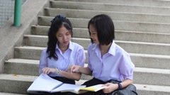 Asian Thai high schoolgirls student couple sit on stairway discussing arguing Stock Footage