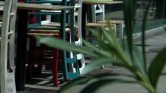 Stockpiled chairs at a market in daytime, with a green plant in the foreground. Stock Footage