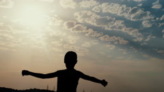 Silhouette on Wind of a Boy on the Background of Sunset Shows How Spacious and Stock Footage