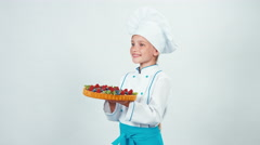 Portrait young baker holding in her hand chocolate cake with sweets and fruit Stock Footage