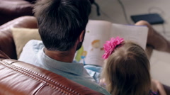 Top view. young father and his little blond daughter are reading a story on Stock Footage