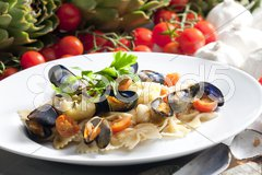 Pasta with mussels, artichokes and cherry tomatoes Stock Photos
