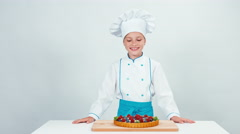 Young chef baker baked chocolate cake with sweets and fruits Stock Footage
