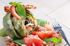 Cooked artichoke with tomatoes, parmesan cheese, pancetta, and mint Stock Photos