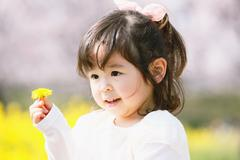 Young smiling Japanese girl enjoying cherry blossoms in a city park Stock Photos