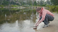 Woman near forest river cleans fish with knife, outdoor Stock Footage