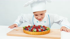 Young chef baker examines chocolate cake with sweets and fruits Stock Footage