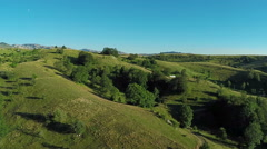 Aerial View, flight over green hills and countryside road and village houses Stock Footage