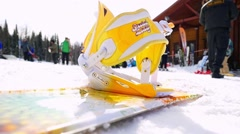 Snowboard lying on the snow in sunny winter day at ski resort in slowmotion Stock Footage