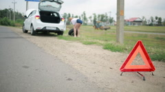 Girl changing a punctured tire at the car. repair of cars on the road. accident Stock Footage