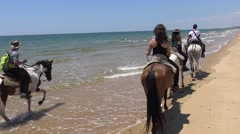 4K Group of women and men cowboys riding horses on a peaceful beach-Dan Stock Footage
