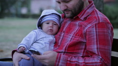 Father with baby is sitting on a bench and send sms Stock Footage