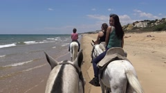 4K Asian Woman Cowgirl riding horses on peaceful beach, ride in the coast -Dan Stock Footage