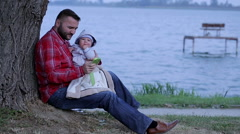 Father is send sms on a phone, sitting with a baby near lake Stock Footage