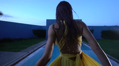 Beautiful brunette woman in yellow dress by the pool Stock Footage