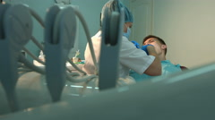 The dentist treats teeth of a young guy. Stock Footage