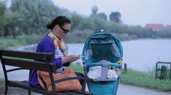 Baby is sleeping on a stroller, mother is send sms on a cellphone Stock Footage