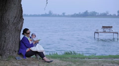 Mother is send sms on a phone, sitting with a baby near lake Stock Footage