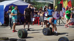 Russia, Novosibirsk, 2016: Bodybuilder puts on weight plate over the bar Stock Footage