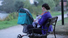 Mother is breastfeeding, sitting on a bench near lake Stock Footage