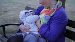 Mother is breastfeeding, sitting on a bench at the park Stock Footage