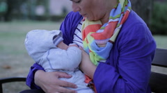 Mother is breastfeeding, sitting on a bench  Stock Footage