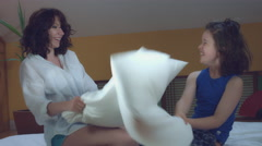4k Morning Shot of a Woman Having Fun with Pillow Fight with her Son in Bed Stock Footage