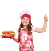 Happy little girl cook with hot dogs and thumb up Stock Photos