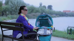 Mother is lulling baby in stroller, sitting on a bench and yawning Stock Footage