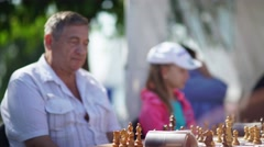 Russia, Novosibirsk, 2016: Middle-aged man plays chess. Chess game Stock Footage