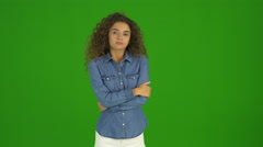 The young curly woman get an idea and stand on the green background. Real time Stock Footage