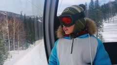 Happy boy in sunglass mask, rises to the top in the cabin cable car at the ski Stock Footage