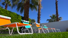 Colorful lawn chairs sit around a pool at a Palm Springs home. Stock Footage