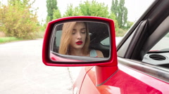 Girl paints her lips while sitting behind the wheel of a car Stock Footage